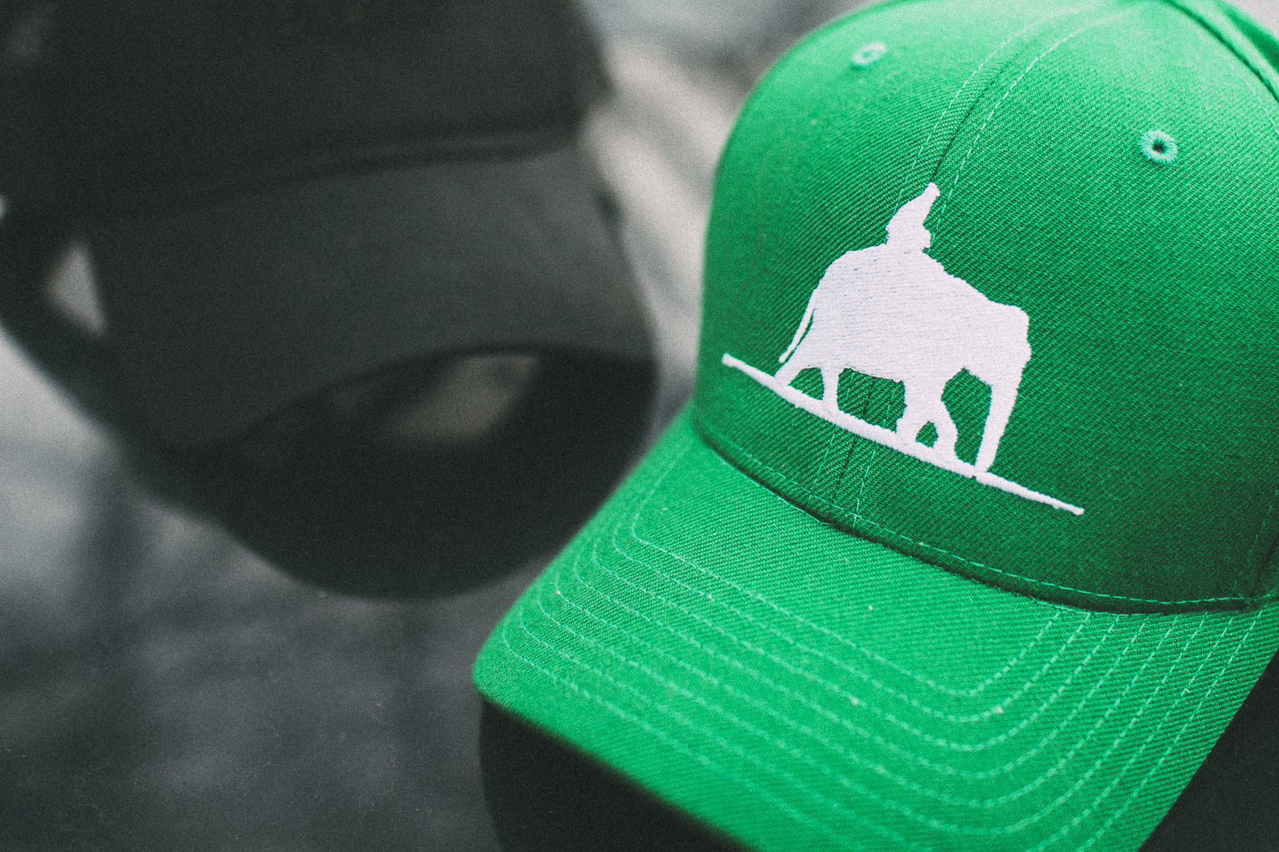 green and black overland empire branded hats caps