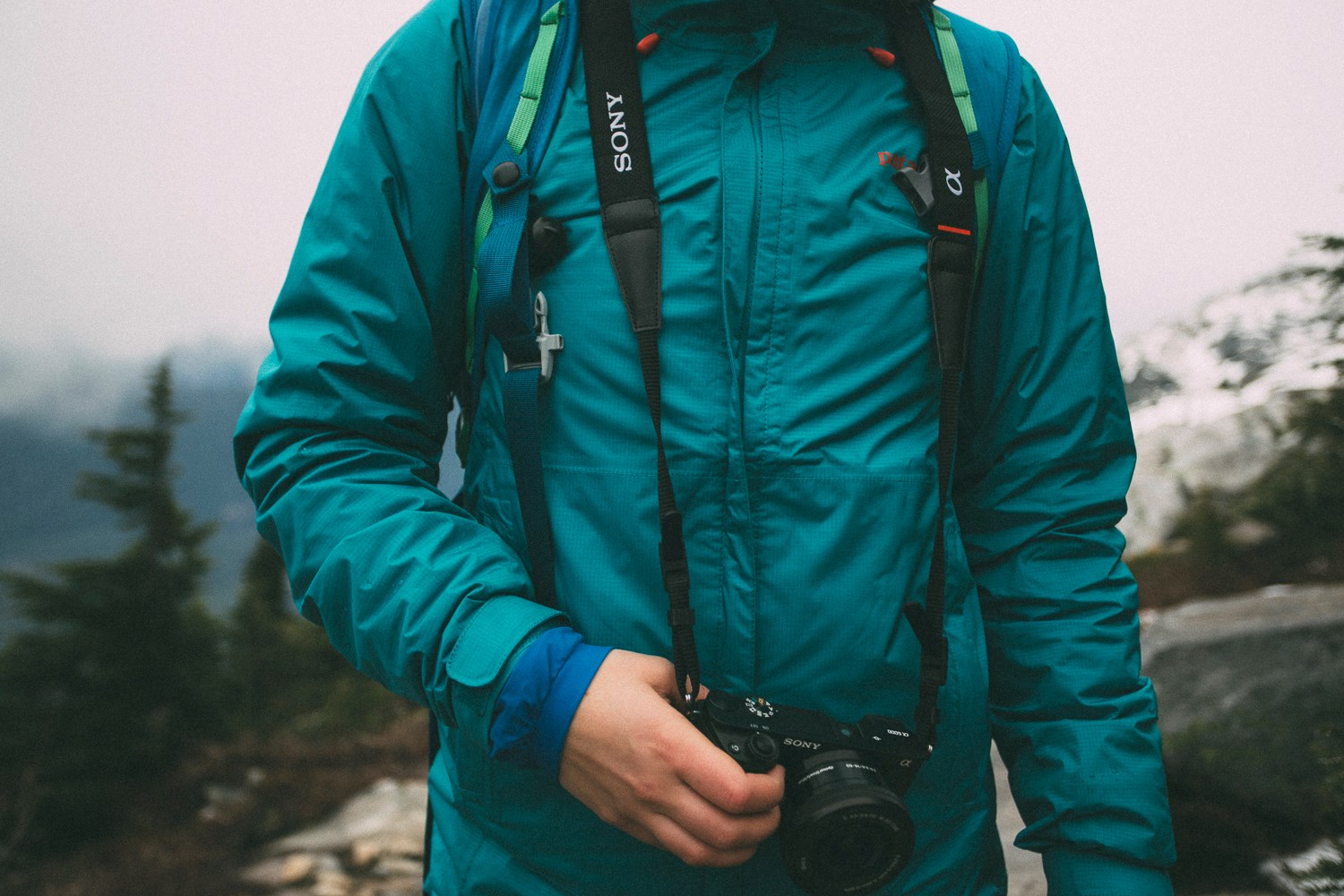 green Patagonia windbreaker jacket with Sony A6000 mirrorless camera south america gear list