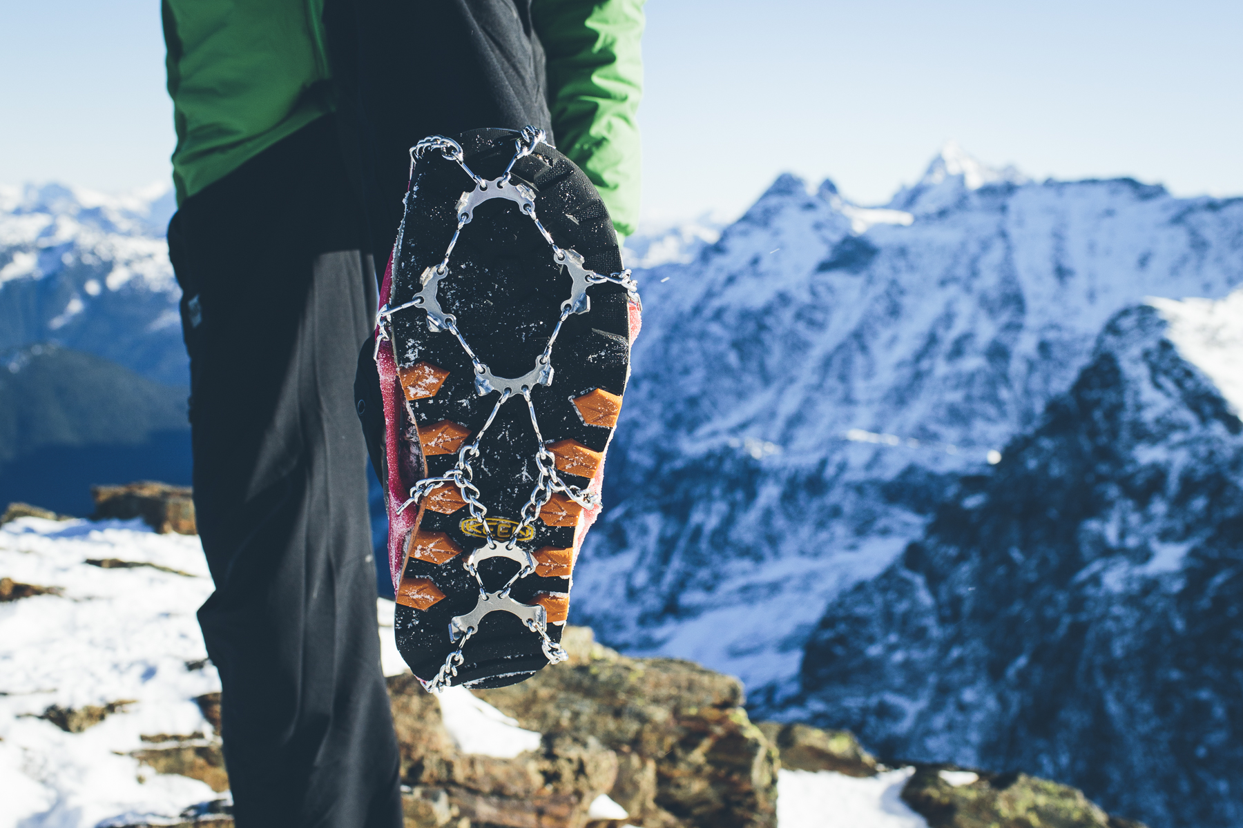 man wearing Kahtoola microspikes on a hiking boot in the mountains with snow south america gearlist