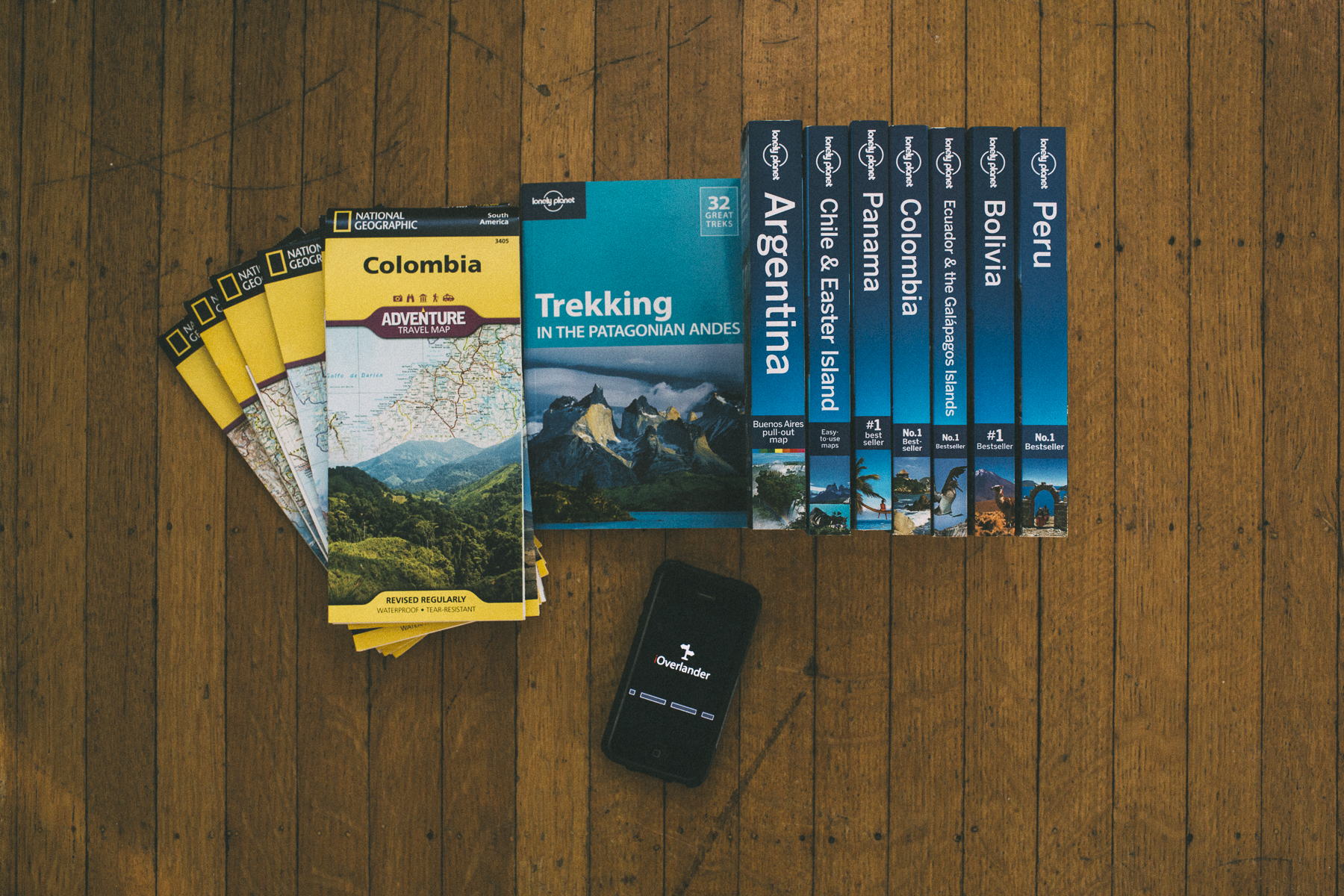 Various National Geographic road maps and Lonely Planet Guidebooks with iOverlander app south america gear list