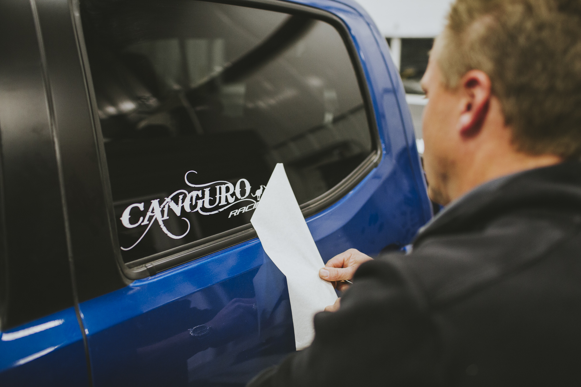 man attaching Canguro Racing decal to Toyota Tacoma